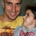 Wolfgang lächelt in die Kamera, seine Tochter Jaël (Trisomie) ist auf seinem Arm und lächelt ihn von der Seite an.