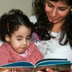 Jaël (Trisomie 18) mit 7 Jahren, auf dem Arm ihrer Mama, schaut sich ein Buch an, das ihre Mama hält.