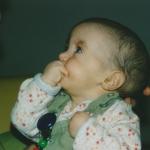 Jaël (Trisomie 18) mit 6 Monaten, schaut ihren Papa an und hat die rechte Hand am Mund.