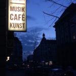 """Leuchtreklame des Prachtwerk mit dem Logo und den Worten """"Musik, Café, Kunst"""""""