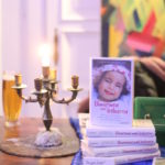 Büchertisch mit einem Stapel unseres Buches »Umarmen und loslassen« und Kerzenleuchter