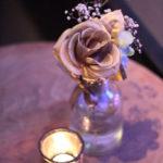 Tisch mit Rose in kleiner Vase und Teelicht davor