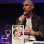 Im Hintergrund Wolfgang Arzt, der ins Mikrofon spricht, im Vordergrund das aufgestellte Buch »Umarmen und loslassen«