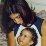 Die zweijährige Jaël (mit Trisomie 18) sitzt auf dem Schoß ihrer Mutter, die beiden lächeln sich an, während sich ihre Blicke treffen.